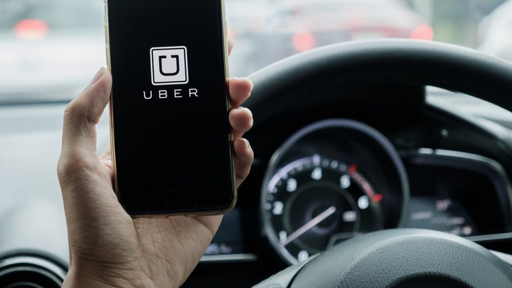A hand holds a phone displaying the Uber app.