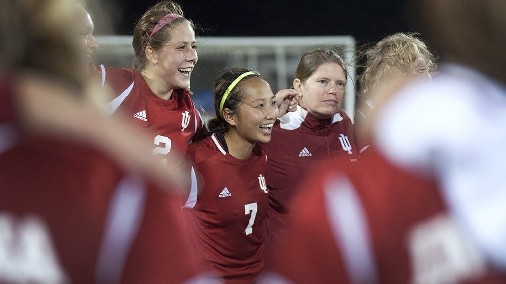 Then-senior Lisa Nouanesengsy, middle, and then-sophomore Jessie Bujouves smile while the team huddles together after IU's match against DePaul on Nov. 16, 2013, at Bill Armstrong Stadium.