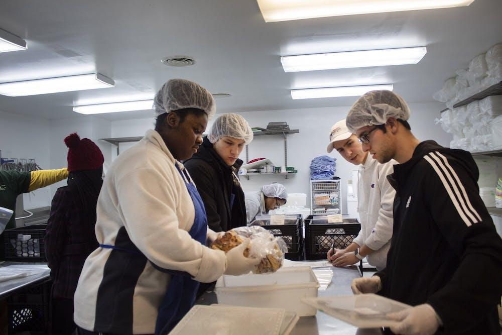<p>IU student volunteers package food Feb. 20, 2019, at Hoosier Hills Food Bank. The food bank increased its distribution of food by 39% in 2020.</p>