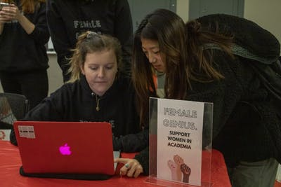 "Freshmen Claire Given, left, and Amber Zhao, right, pass out sweatshirts Dec. 6, 2019, in Hodge Hall. The Women In Business organization sold sweatshirts that said ""Female Genius."" as a fundraiser for Girls Inc."
