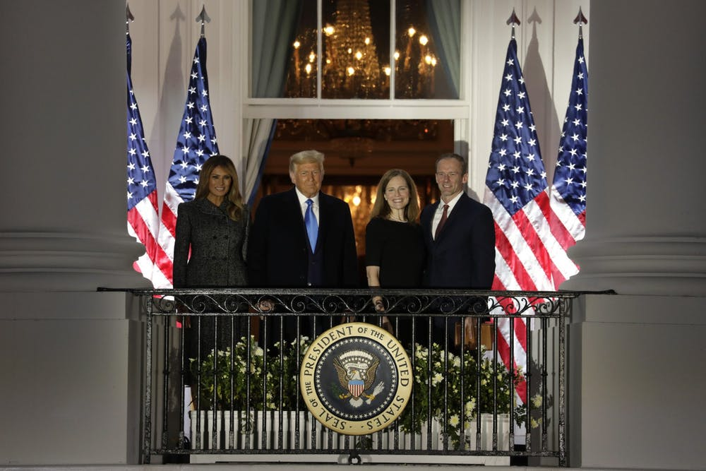 <p>President Donald Trump with First Lady Melania Trump and new Supreme Court Associate Justice Amy Coney Barrett with her husband Jesse Barrett face guests after she was sworn in during a ceremony on the South Lawn of the White House on Oct. 26 in Washington, D.C.</p>