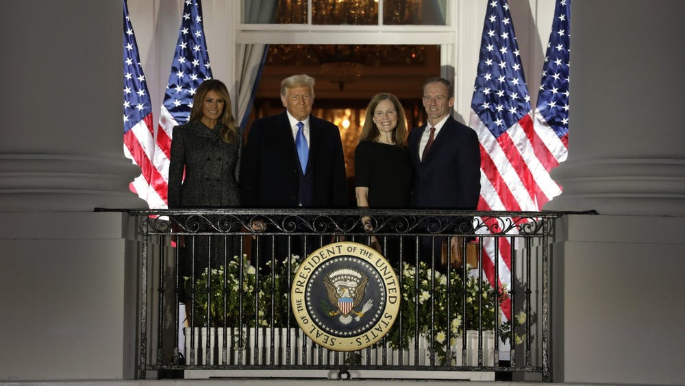 President Donald Trump with First Lady Melania Trump and new Supreme Court Associate Justice Amy Coney Barrett with her husband Jesse Barrett face guests after she was sworn in during a ceremony on the South Lawn of the White House on Oct. 26 in Washington, D.C.