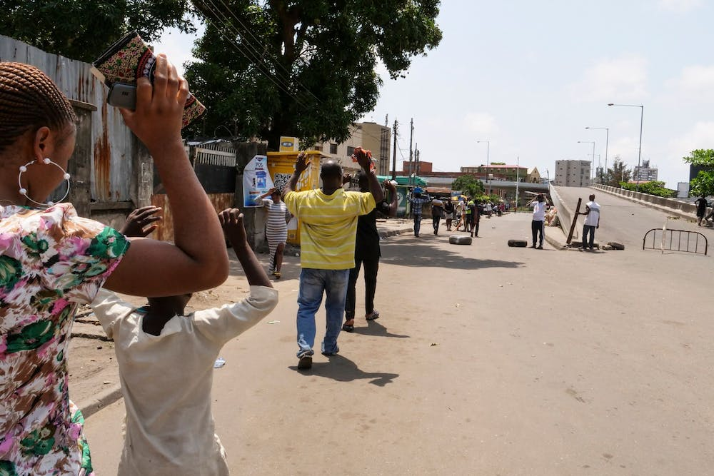 <p>People are obligated to walk with their hands upon their heads as they pass security checkpoints Oct. 23 at Obalende Market, Lagos, Nigeria. </p>