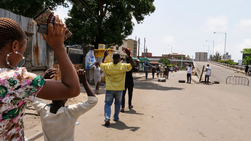 People are obligated to walk with their hands upon their heads as they pass security checkpoints Oct. 23 at Obalende Market, Lagos, Nigeria.