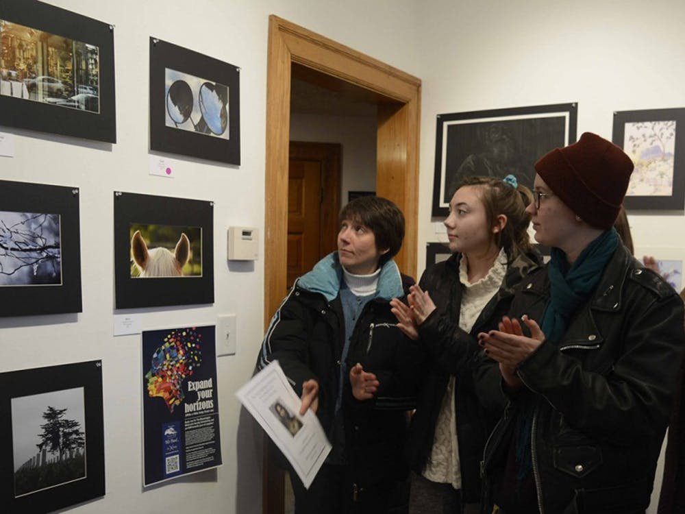 Visitors are celebrating the best photography award during the Juried Arts student show at The Venue, Fine Art & Gifts during the Juried Arts student show, Jan 29.
