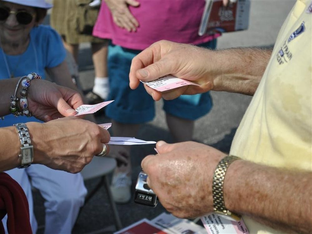 A volunteer collects tickets at the main entrance.