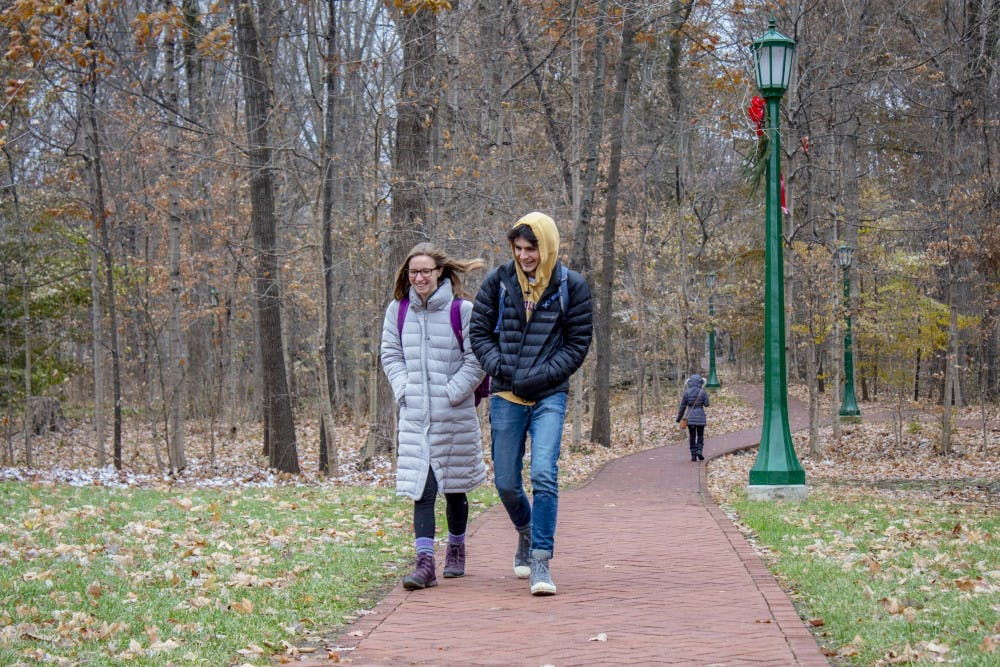 <p>IU students Emma Schuster and Adam Diersing walk through Dunn's Woods on Nov. 26.&nbsp;</p>