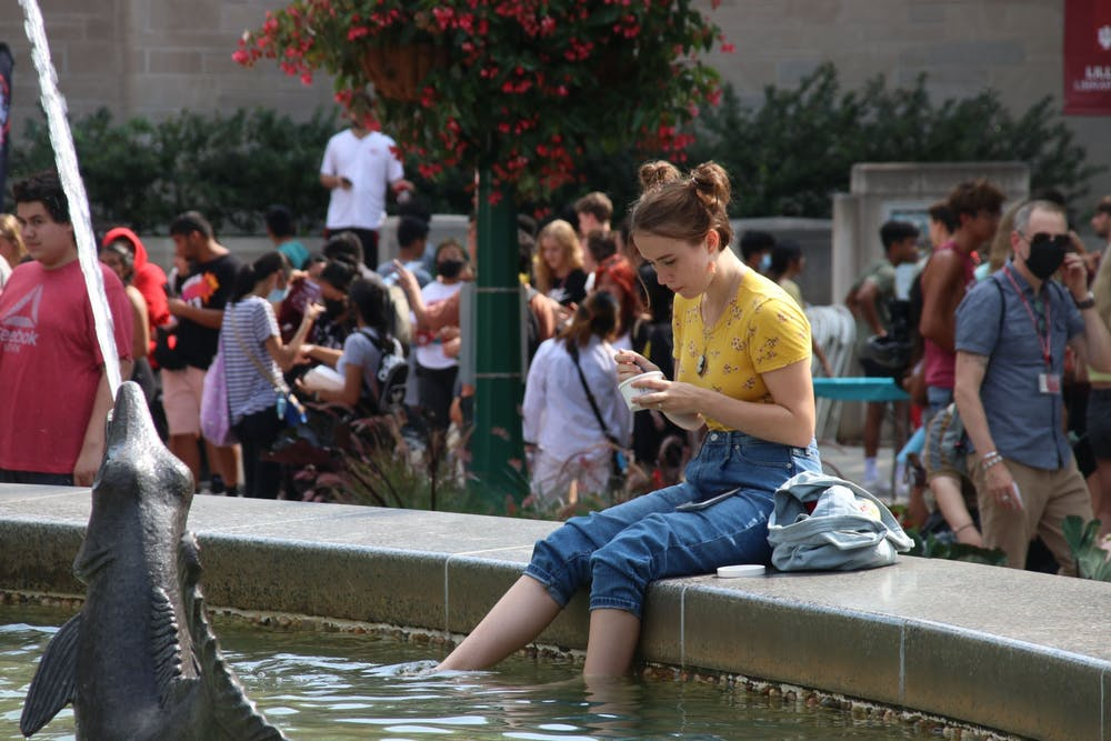 <p>Freshman Estella Borden eats ice cream Aug. 19 while dipping her feet in Showalter Fountain during CultureFest. The welcome week event consisted of numerous booths, food trucks and live performances. </p>