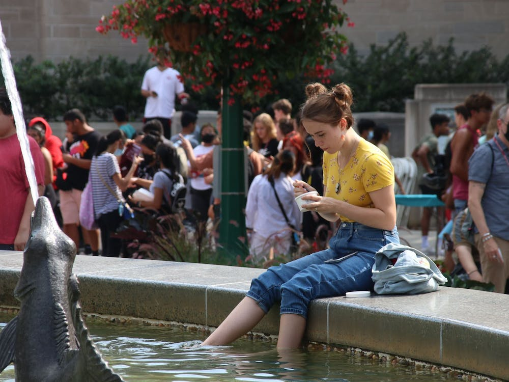 Freshman Estella Borden eats ice cream Aug. 19 while dipping her feet in Showalter Fountain during CultureFest. The welcome week event consisted of numerous booths, food trucks and live performances.