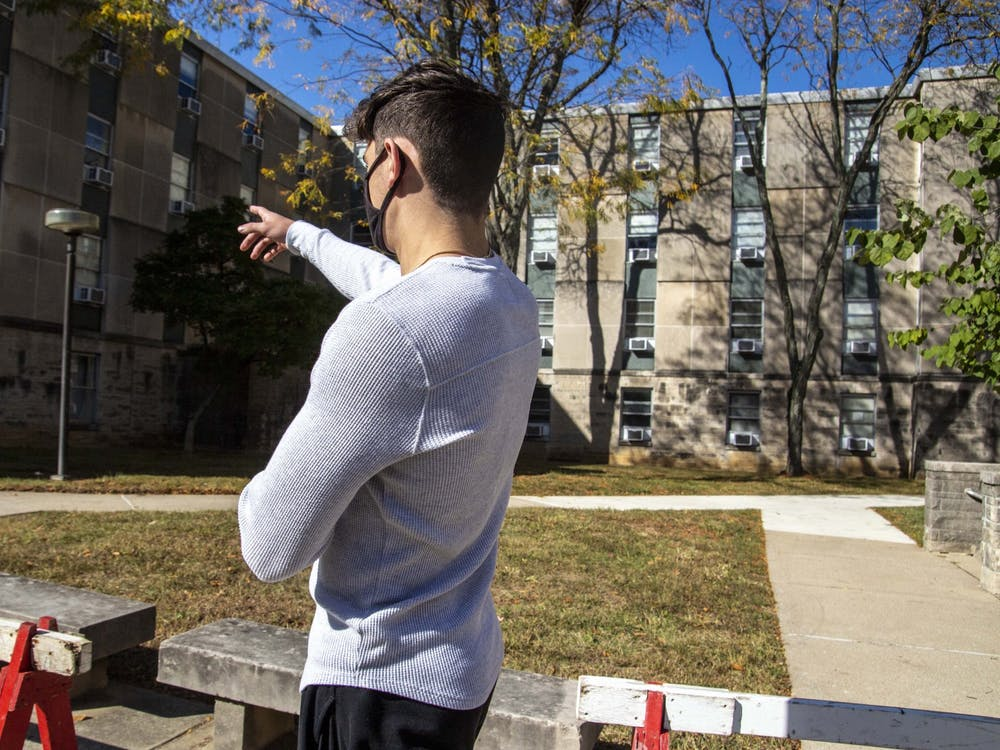 Freshman Tommy Reynolds points at the room he spent his quarantine period in Oct. 16 at Ashton Residence Center. Reynolds said he's worried IU is limiting student freedoms too much during the pandemic, but he is thankful measures were taken to allow him to have an on-campus experience this semester.