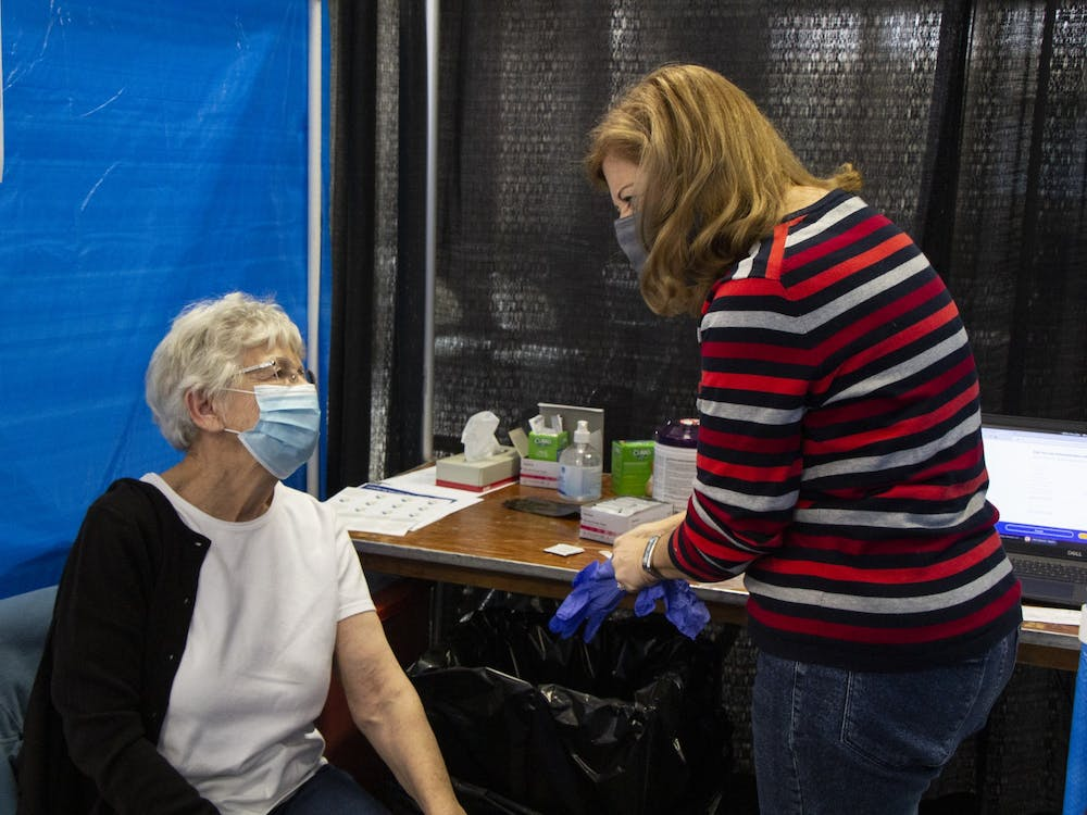 IU Health nurse Anne Fuson puts on gloves before giving Iva Gloss the second dose of the Moderna COVID-19 vaccine Feb. 24 at the Monroe Convention Center. Monroe County Health Department administrator Penny Caudill said the vaccination process usually takes about 20 minutes.