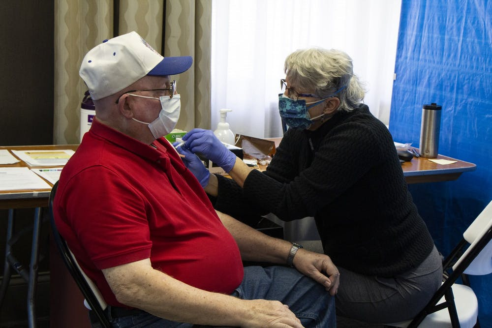 <p>Nurse Cathy Green gives Raymond Lamar his second dose of the Moderna COVID-19 vaccine Feb. 24 at the Monroe Convention Center.<strong> </strong>Indiana has lowered the eligibility age for vaccinations to 50, marking the second time this week the eligibility age was lowered, Gov. Eric Holcomb said.</p>