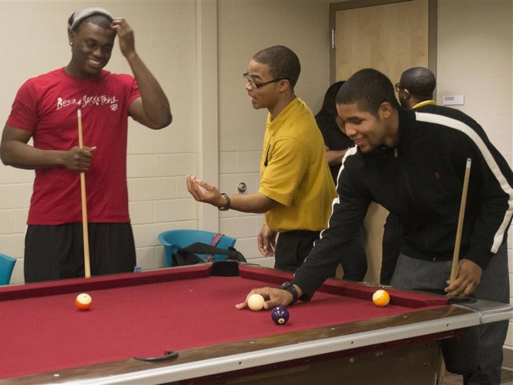 Students play pool during the celebration of the founding anniversary of the Gamma Eta Chapter of Alpha Phi Alpha on Wednesday in Briscoe Quad.
