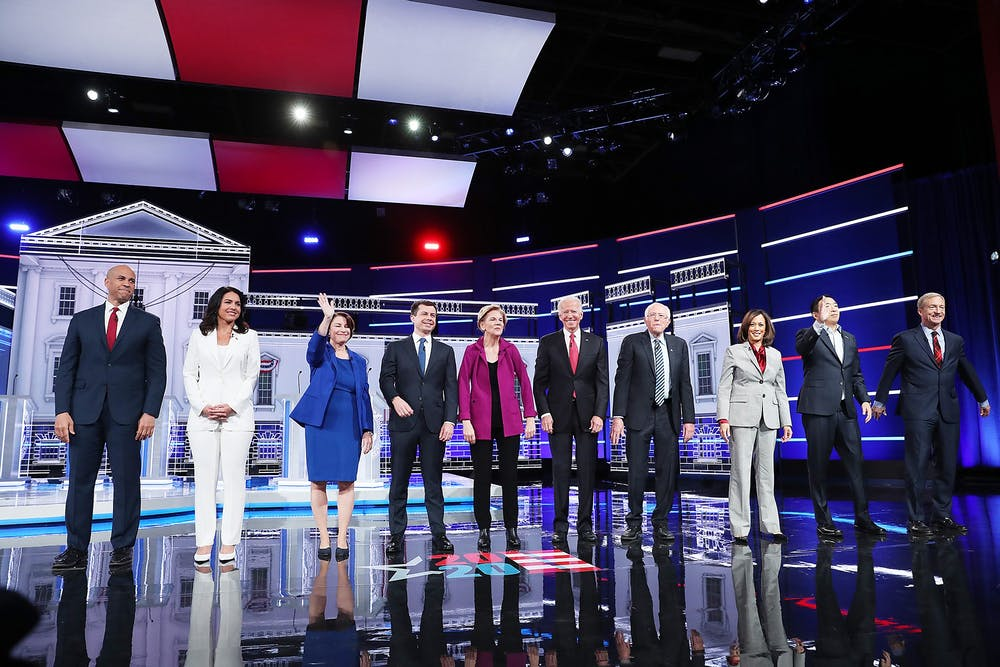 <p>Democratic presidential candidates arrive on stage before the start of the Democratic presidential debate Wednesday at Tyler Perry Studios in Atlanta.</p>
