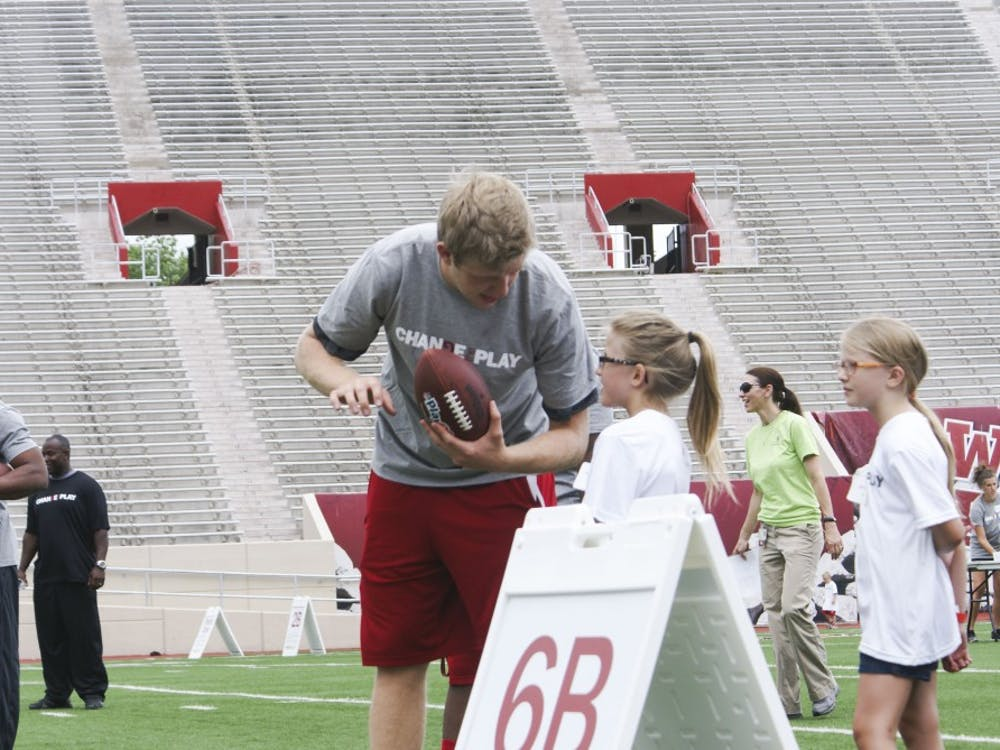IU quarterback Nate Sudfeld talks with a young girl before he throws her a pass at the Change the Play event Tuesday in Bloomington.