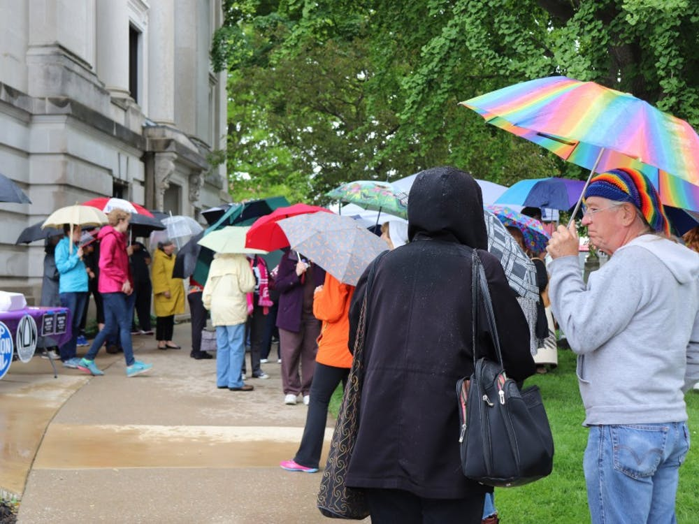 A crowd gathered around 12 p.m. on May 21 at the Monroe County Courthouse.Protesters stand under umbrellas while waiting for the rally to begin.