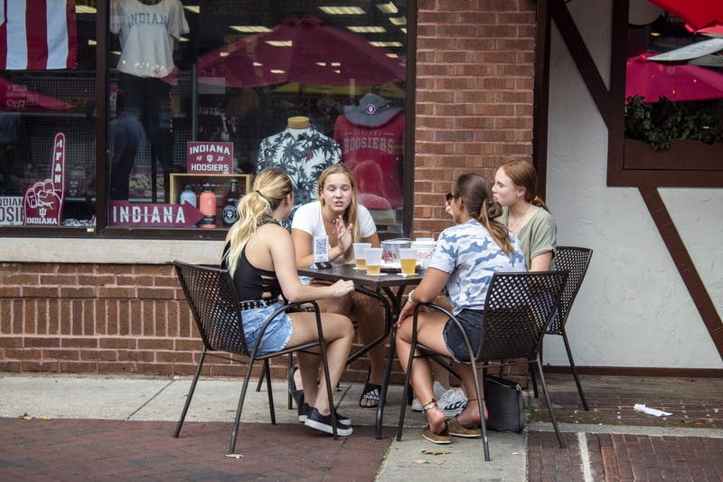 A group of friends sit outside Aug. 29 in front of Nick's English Hut. Nick's is one of several restaurants taking advantage of the Kirkwood Avenue closure to move more seating outdoors on the weekends.