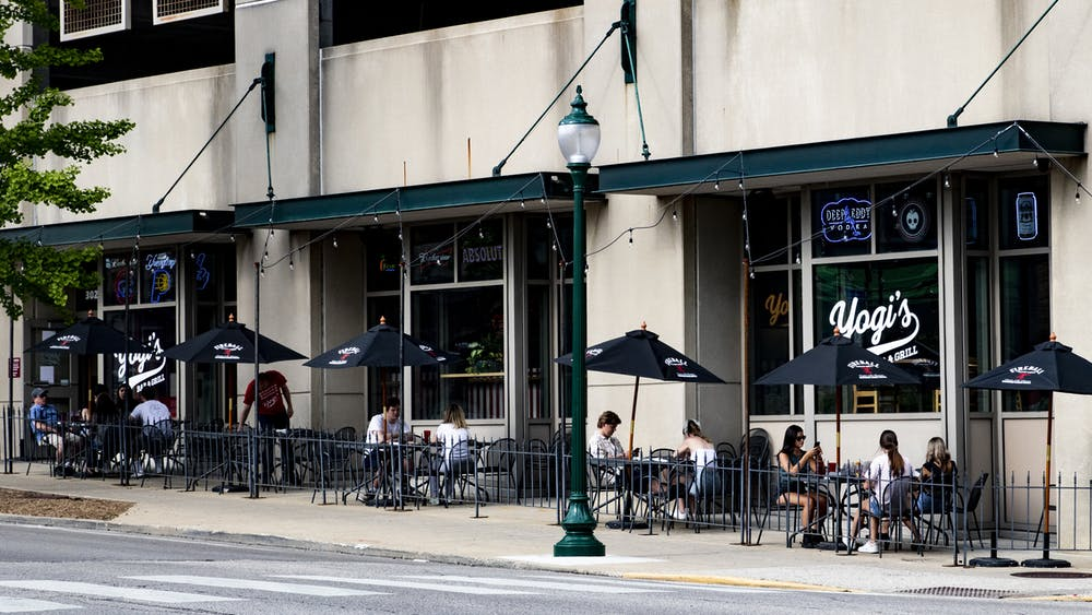People sit outside of Yogi's Bar and Grill on May 16 in Bloomington. Indiana stores and bars are beginning to reopen with restrictions and regulations to promote social distancing.