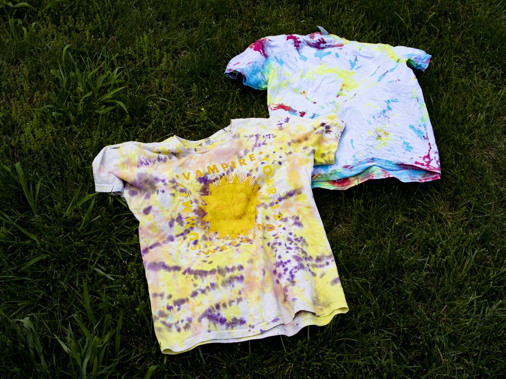 Tie-dyed shirts lay in the grass May 27. After staining for six to eight hours, the shirts were washed in warm water separately and left in the sun to dry.