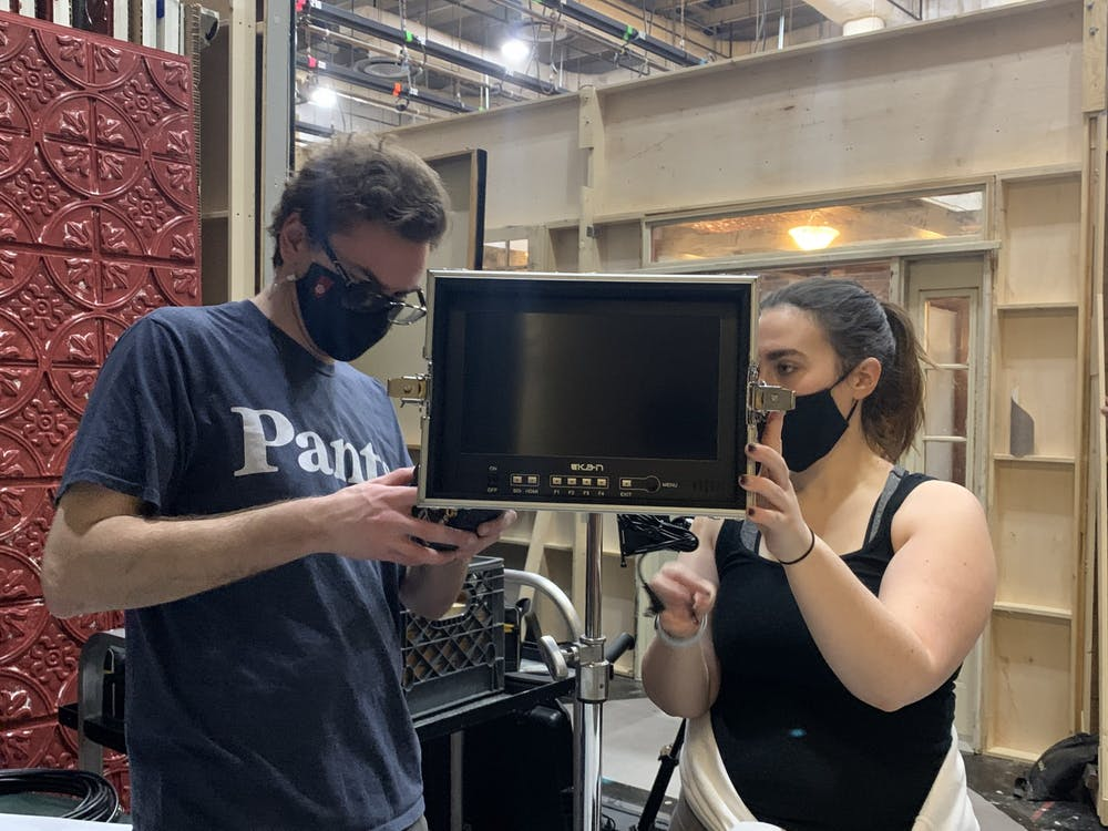 Senior Andrew Phillips and junior Emma Bloomfield look at equipment in their Intermediate Motion Picture Production class Monday in the Radio TV Building. IU President Michael McRobbie announced Feb. 24 that classes will be in person for the fall semester.