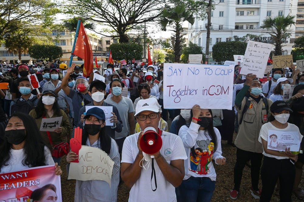 <p>Protesters hold signs during a demonstration against the military coup on Feb. 11, 2021 in front of the Central Bank of Myanmar in Yangon. Indiana is home to one of the largest Burmese refugee populations in the United States.</p>