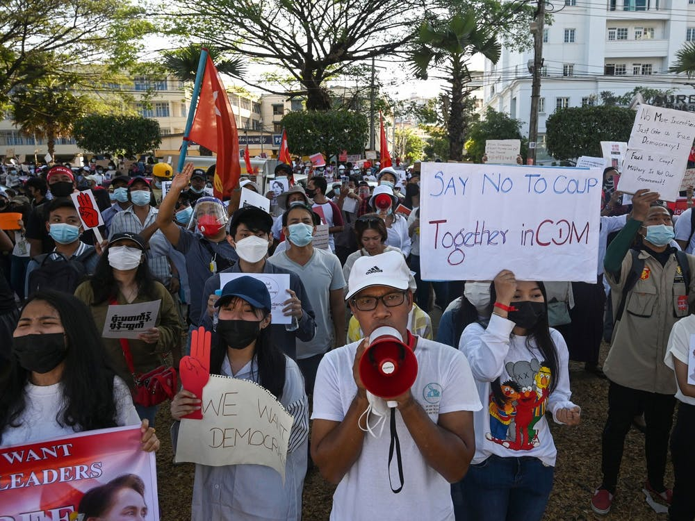 Protesters hold signs during a demonstration against the military coup on Feb. 11, 2021 in front of the Central Bank of Myanmar in Yangon. Indiana is home to one of the largest Burmese refugee populations in the United States.