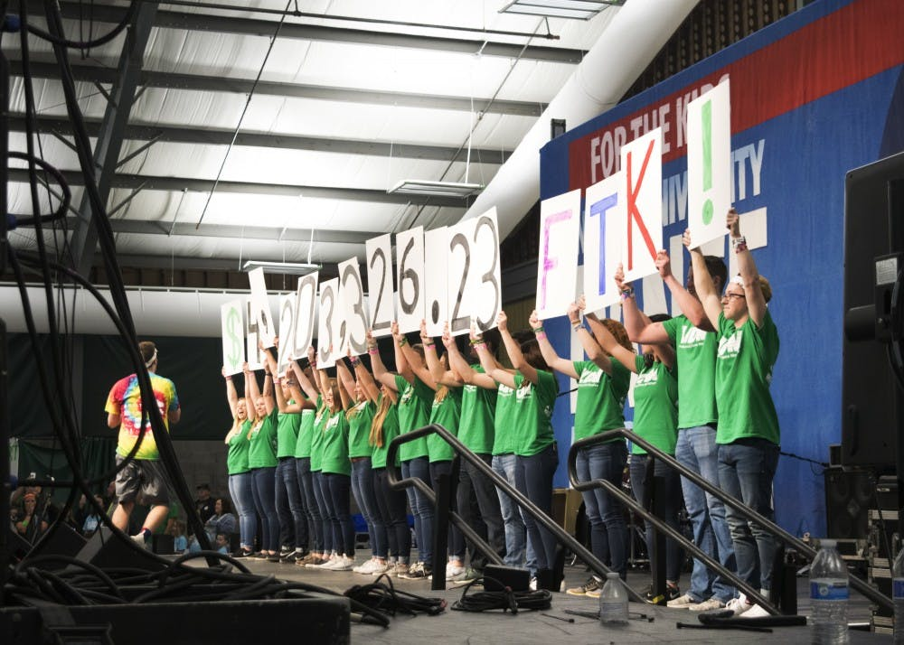 <p>IUDM participants reveal signs displaying the total amount fundraised. The 2017 IUDM raised $4,203,326.23 for the kids.</p>