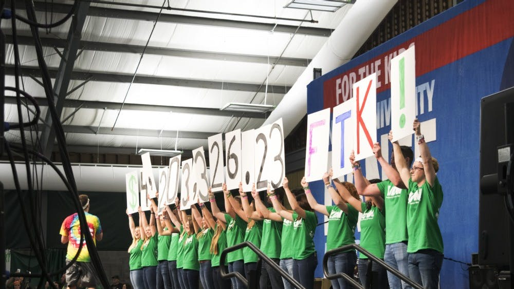 IUDM participants reveal signs displaying the total amount fundraised. The 2017 IUDM raised $4,203,326.23 for the kids.