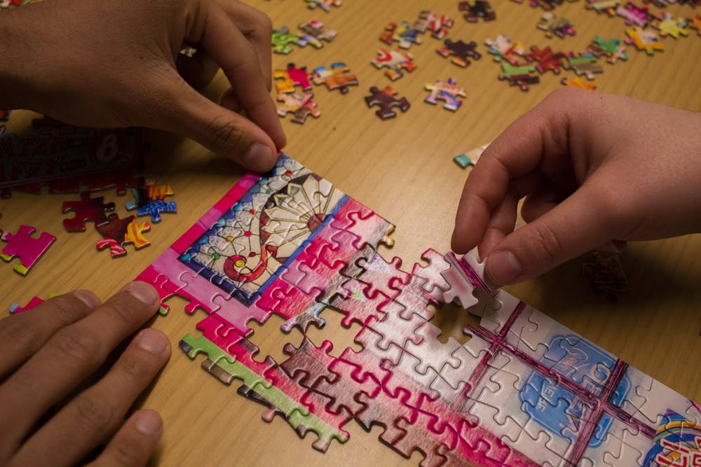<p>Students put together part of a puzzle Jan. 29 inside Franklin Hall. The fifth annual Monroe County History Center PuzzleFest will take place at 10 a.m. Feb. 1 in the Girls Inc. of Monroe County gymnasium.</p>