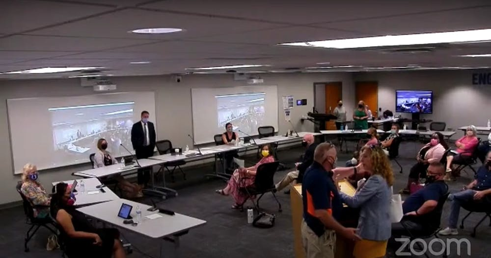 <p>Monroe County Community School Corporation resource officer attempts to motion Margaret Menge out of a school board meeting after she refused to follow indoor masking protocols. The affair sparked a recess during the Aug. 24, 2021 meetingat the Administration Center on 315 E. North Drive.<br/></p>