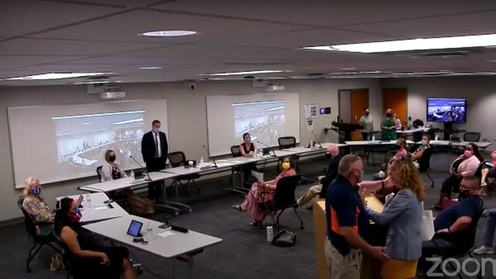Monroe County Community School Corporation resource officer attempts to motion Margaret Menge out of a school board meeting after she refused to follow indoor masking protocols. The affair sparked a recess during the Aug. 24, 2021 meetingat the Administration Center on 315 E. North Drive.