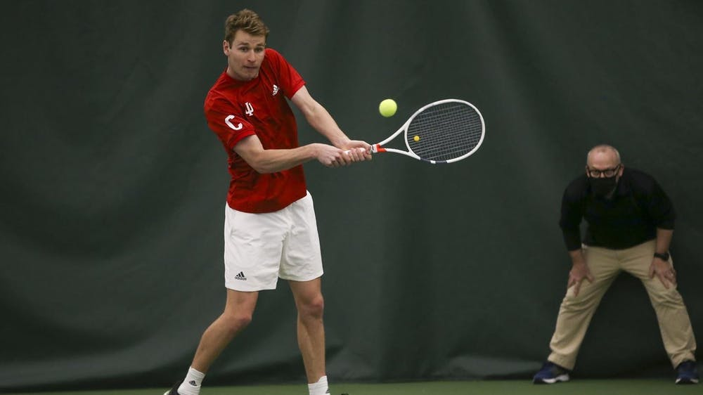 <p>IU graduate student Bennett Crane swings his racket in a game against Michigan on April 3. The Hoosiers will play against the Penn State Nittany Lions on Saturday.</p>
