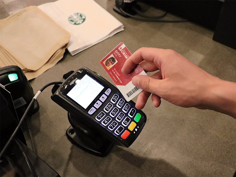 A student gets ready to swipe their Crimson Card at a dining hall.