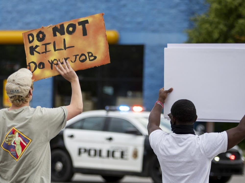 Protesters hold signs as they walk toward police cars June 1 on Third Street.