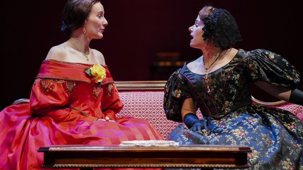 """Catherine Sloper, left, and aunt Lavinia Penniman, right, portrayed by Glynnis Kunkel-Ruiz and Ellise Chase, socialize before a party during a rehearsal of Ruth and Augustus Goetz """"The Heiress"""" on Sept. 18 in Ruth N. Halls Theatre. The story focuses on Catherine Sloper, a wealthy, socially awkward woman who falls in love with a man that her father believes is only after their money."""