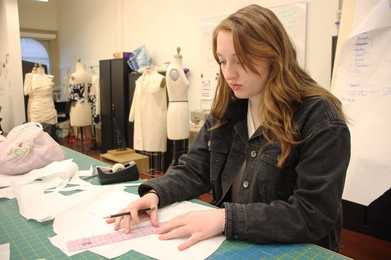 Junior Meredith Higgins, a fashion design major, sketches her pieces Feb. 24 in Kirkwood Hall. Higgins designed a fashion line for her senior collection.