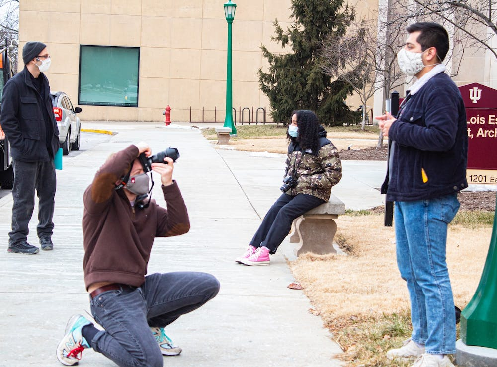 <p>Junior Tyler Richardson takes a picture of senior Max Eslava for their photography class Feb. 8 outside of the IU Fine Arts Building. IU President Michael McRobbie announced in February that the university is set to return to mostly normal operations for the fall 2021 semester because of lower COVID-19 positivity rates and the availability of vaccines.</p>