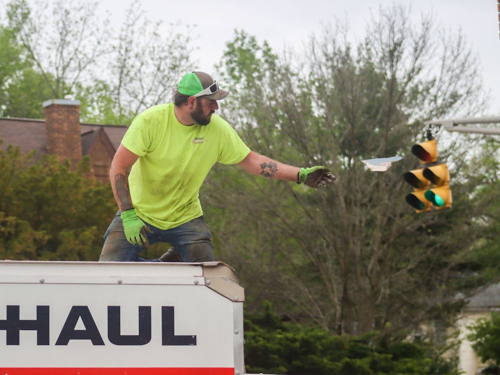 An employee of Kent's Westside Service and Towing throws a piece of brick off the U-Haul van Sunday night. The van crashed into local tattoo and piercing parlor Evil by the needle around 4:45 p.m. Sunday.