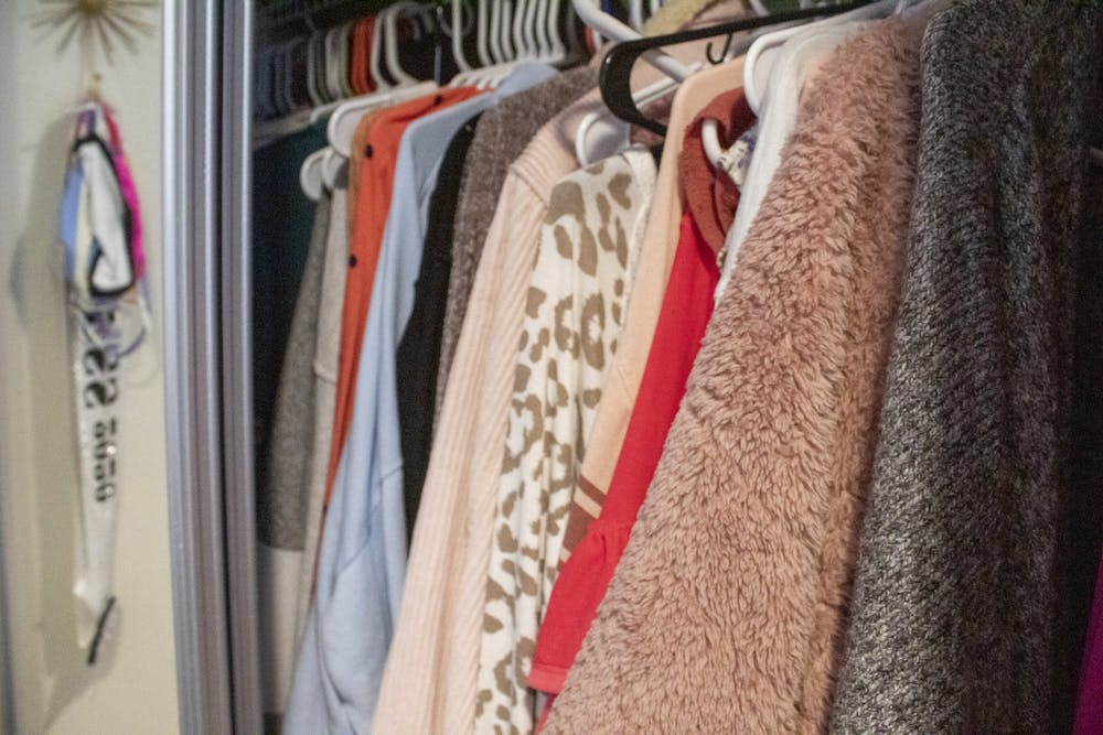 <p>Clothing items hang in a closet Oct. 11 in an off-campus apartment. When moving into college, it is important to think about how much closet space you will have while deciding how many clothes to pack.</p>