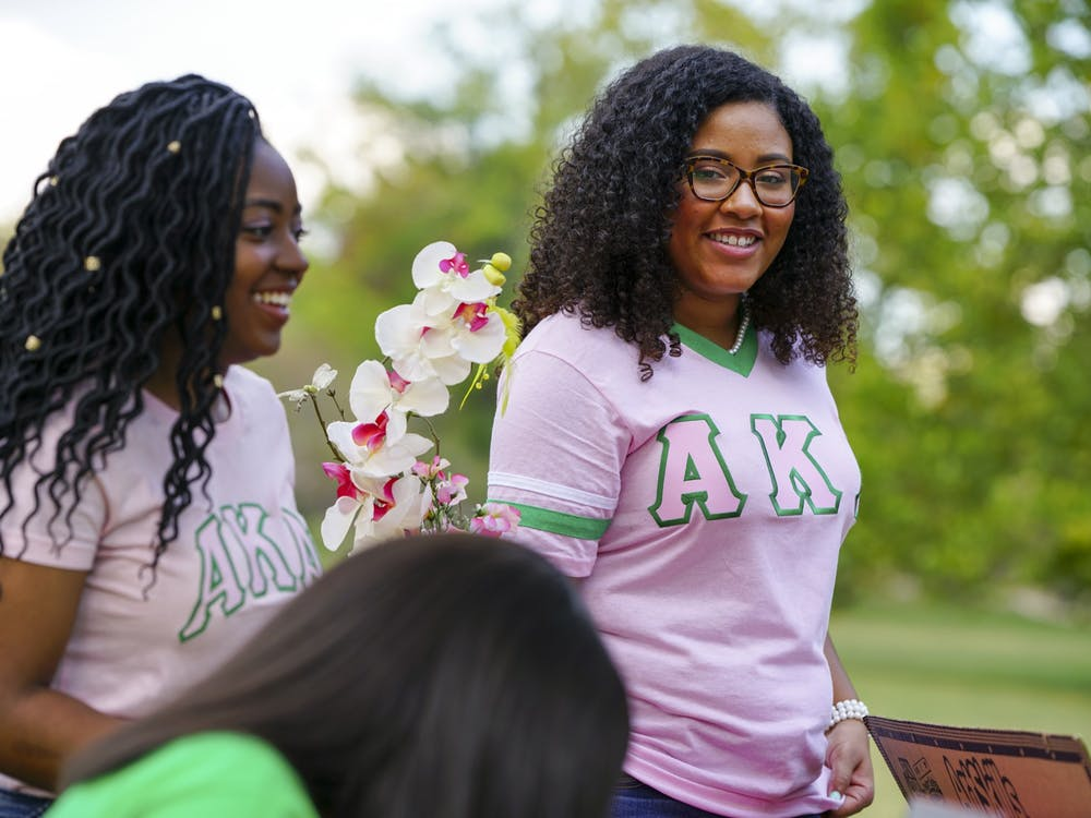 Alpha Kappa Alpha sorority members wait for prospective sisters to visit their table Sept. 16, 2017, during IU's National Pan-Hellenic Council fair in Dunn Meadow.