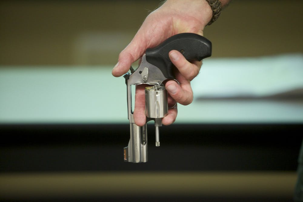 <p>A person holds a Smith &amp; Wesson .357 magnum revolver with the cylinder open.</p>
