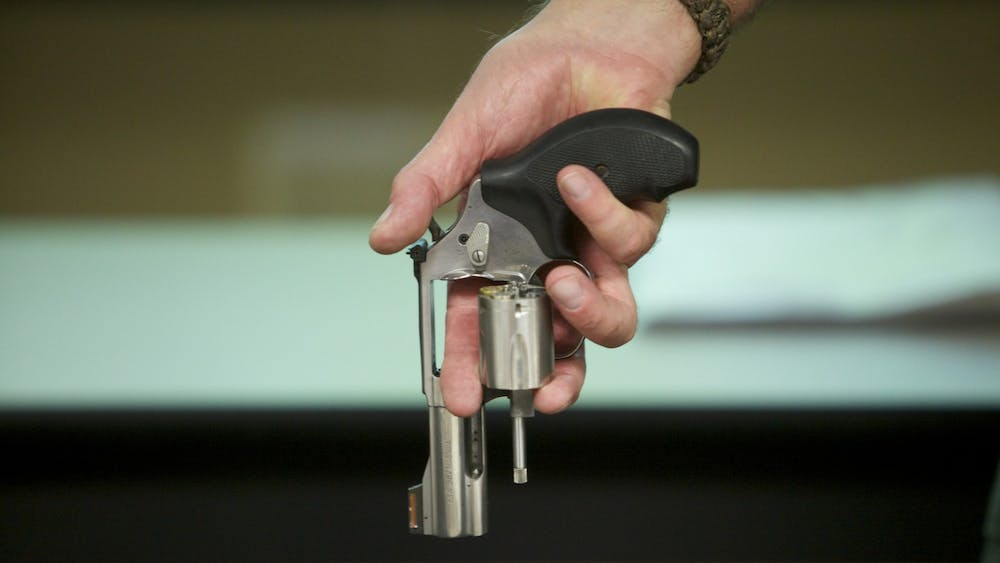 A person holds a Smith & Wesson .357 magnum revolver with the cylinder open.