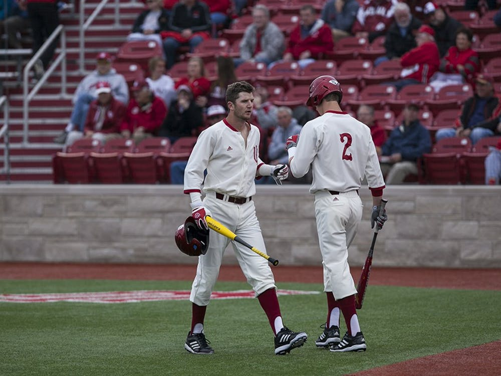 Designated hitter Brad Hartong is congratulated by teammate Logan Sowers after scoring a run on Wednesday at Bart Kaufman Field.