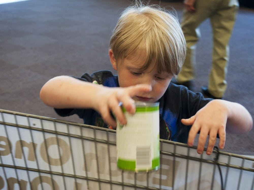 Lorenzo Molica places a can in the cart Saturday for Monroe County United Ministries food drive at Kroger. The goal for the food drive was to collect 16 thousand pounds of food in three days.
