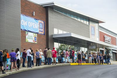 People stand in line Aug. 22 at the grand opening of Aldi on East Third Street. The line to get into the store wrapped around the side of the store and down Williamsburg Drive.