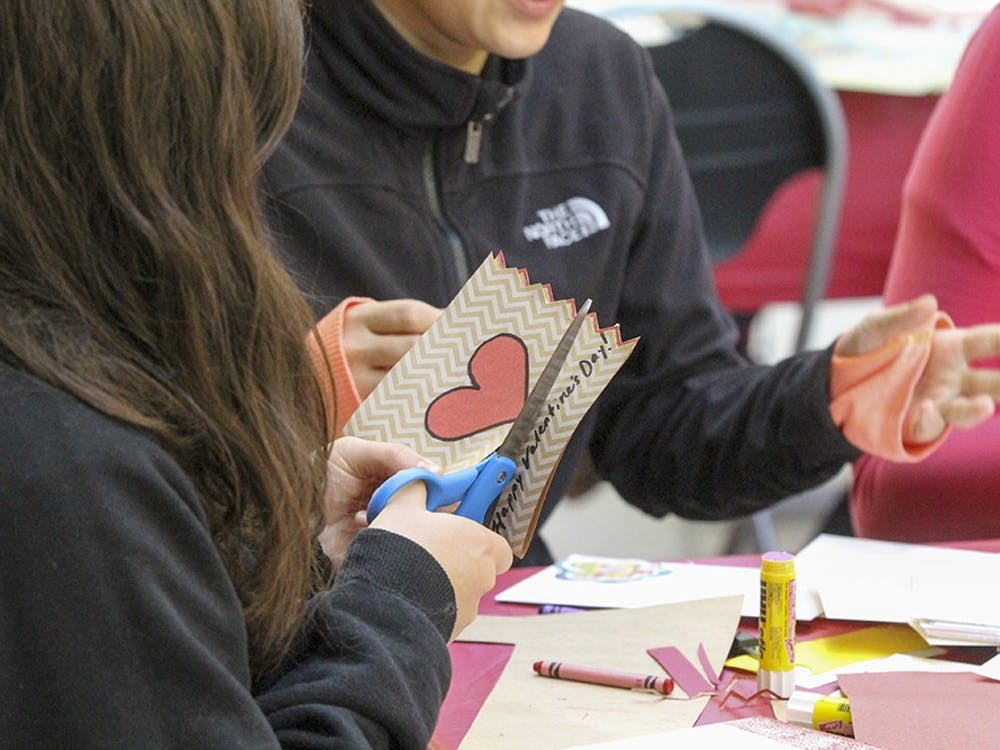 Freshman Grace Buchan makes Valentine's Day cards with a group of other students in the Art Museum atrium as part of the HeART Valentine's Day celebration.