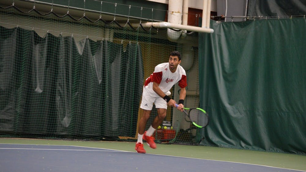JuniorRaheelManji dives for the ball during the Hoosiers' tennis match against Louisville on Feb. 8. Manji won both his singles and doubles match Thursday, but IU lost in the first round of the Big Ten Tournament to Minnesota.