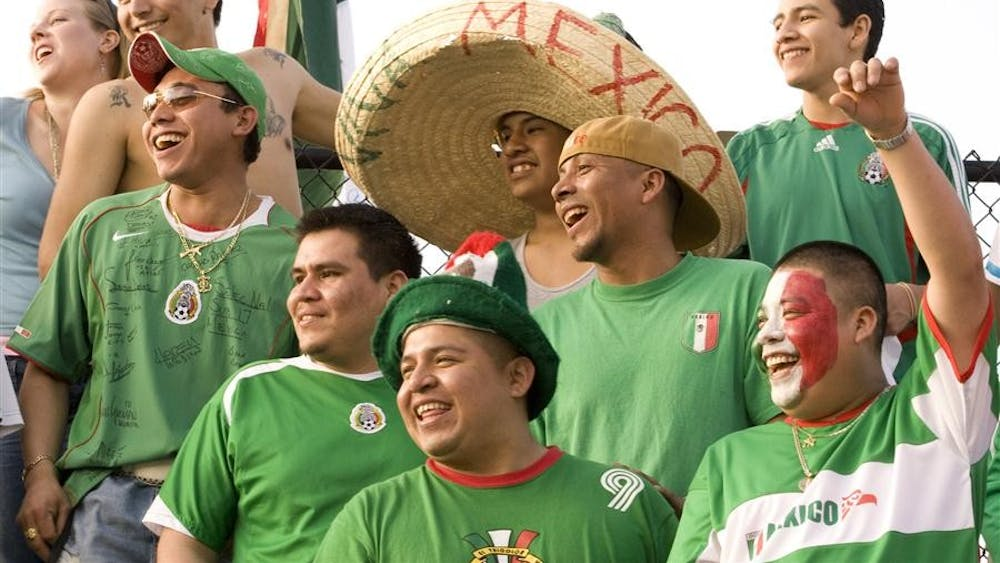 Mexican fans laugh at one of their comrades before the annual soccer match between the IU men's soccer team and the Mexican Youth National Team. Throughout the entire match, the Mexican fans showed their intense love for the sport by running their country's flag around Bill Armstrong Stadium to twirling noisemakers and blowing air horns when they deemed necessary.
