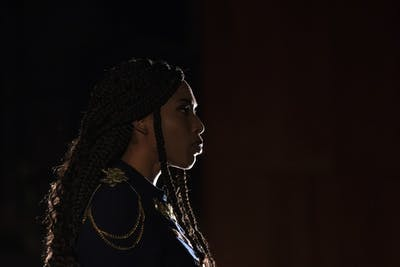 "Actress Adrianne Embry looks out during the final scene of ""Hamlet"" on Dec. 3 in Ruth N. Halls Theater. Embry is a founding member of the group BBBTT, or Black Brown & Beige Theater Troupe, whose goal is to promote the inclusion of people of color in the IU theater department."