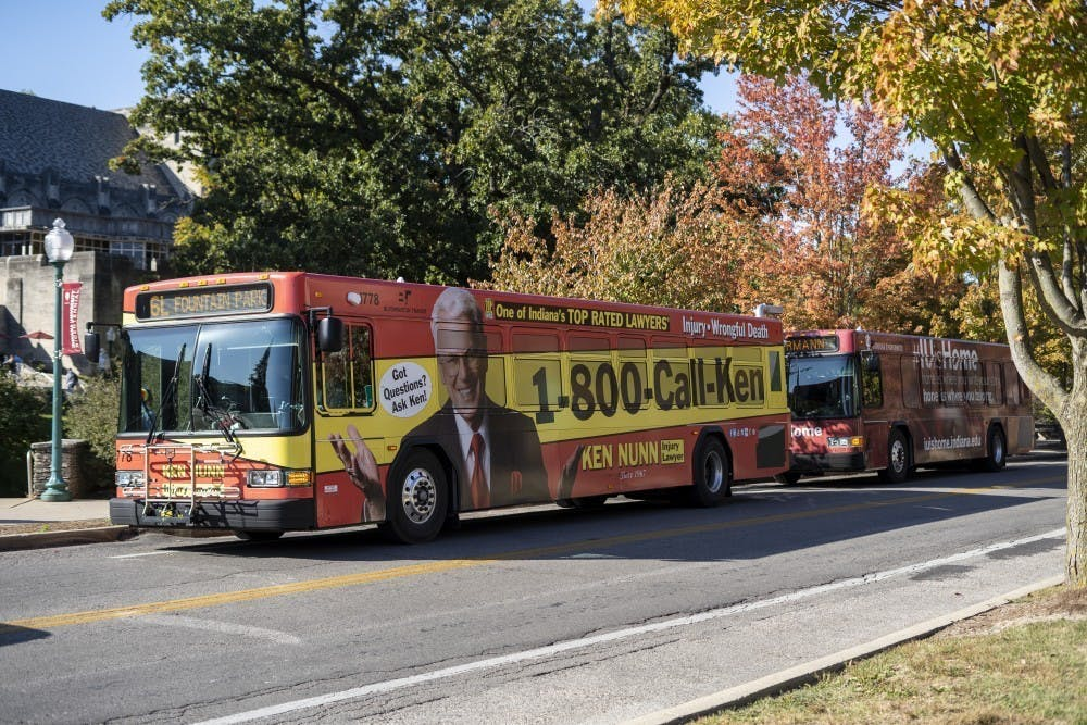 <p>Two Bloomington Transit buses wait to pick up students Oct. 15, 2019, on East Seventh Street. Bloomington Transit has postponed approving all service changes.</p>